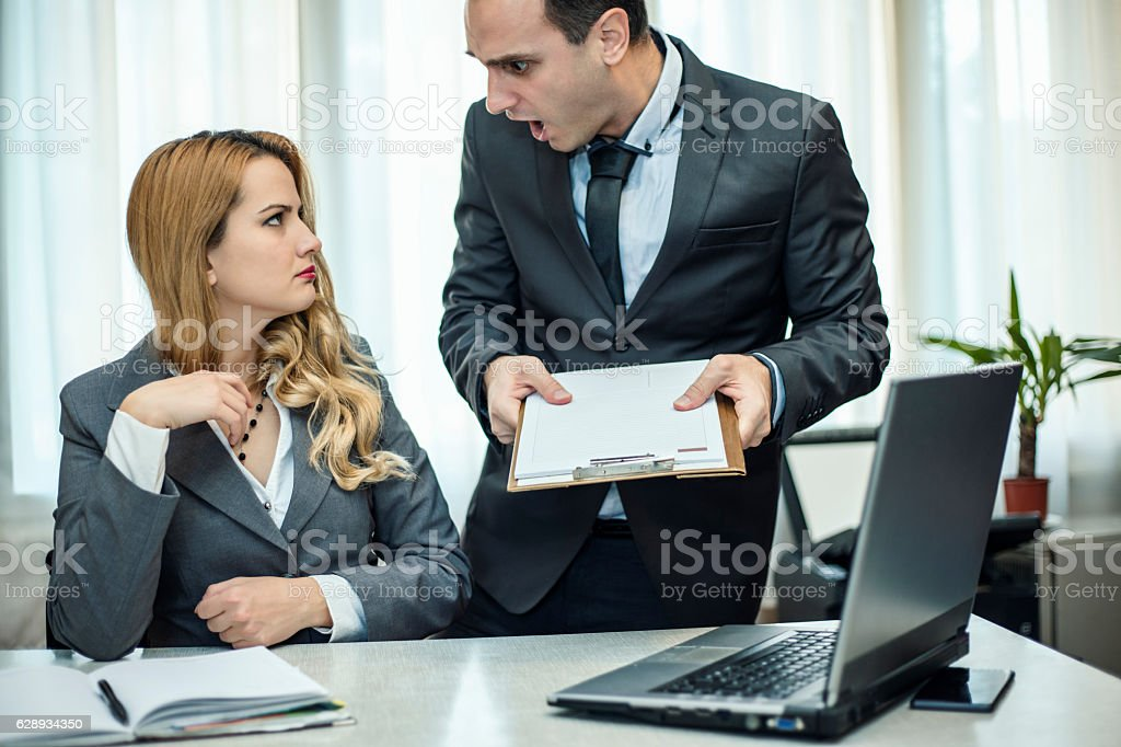 Angry manager scolding his subordinate at the office. stock photo