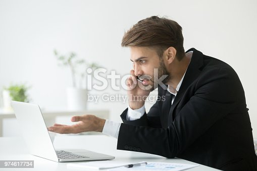 857213750istockphoto Angry manager talking over phone solving company problems 974617734