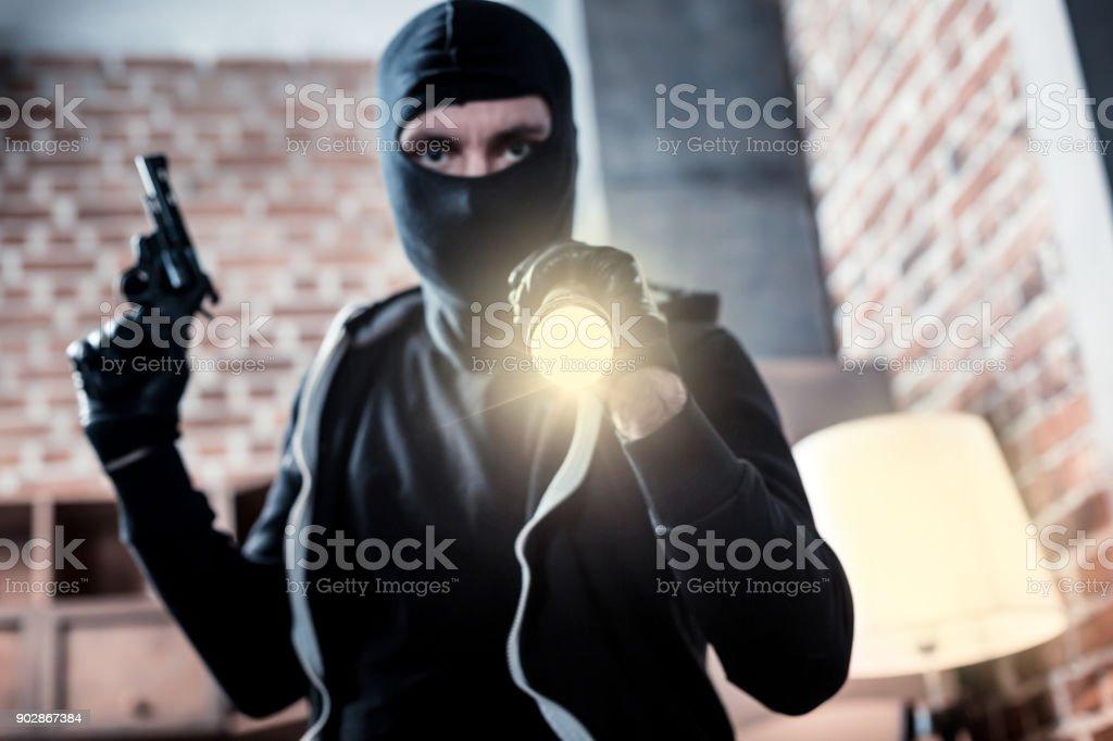Ladrão mascarado com raiva, segurando uma tocha e uma arma - foto de acervo