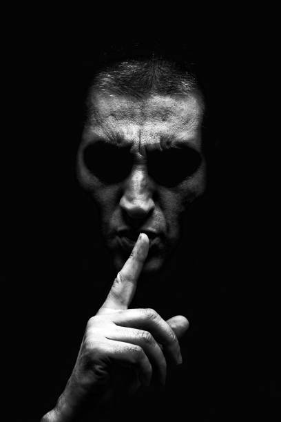 Angry mature man with an aggressive look making the silence sign in a threatening and creepy way. Angry mature man with an aggressive look making the silence sign in a threatening and creepy way. Black and White, black background. Concept for secret, threat, anger, rage, violence, danger, menace. stranger stock pictures, royalty-free photos & images