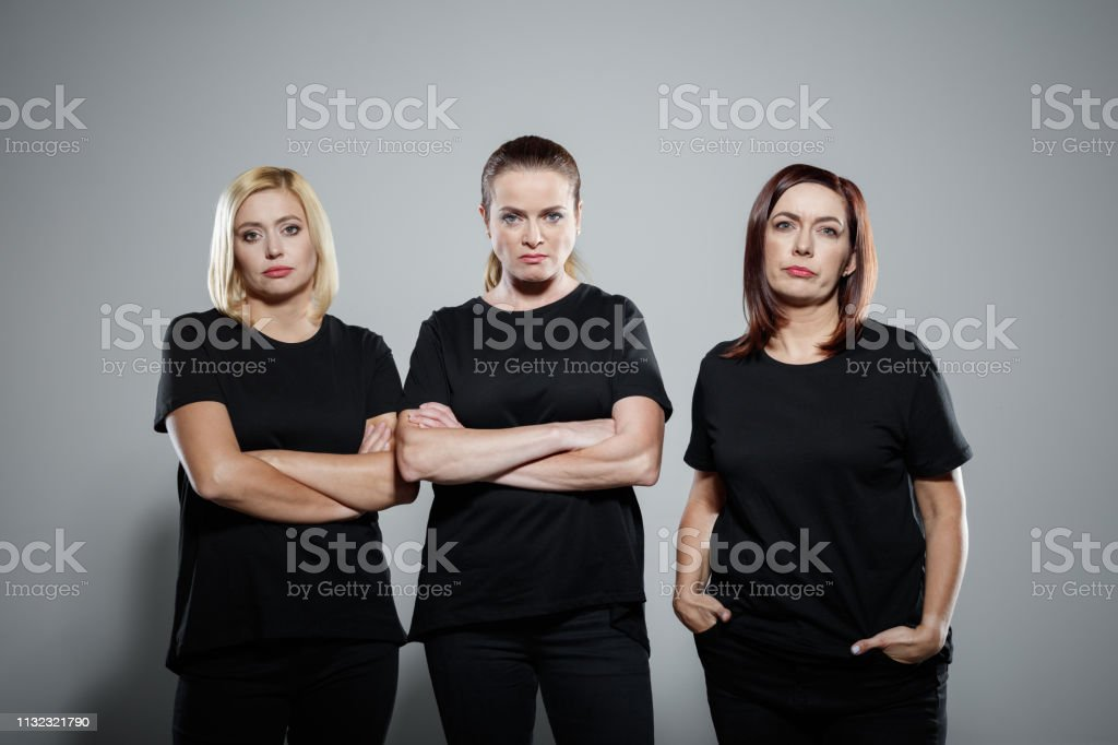 Angry mature women wearing black clothing Portrait of determined mature women wearing black clothing. Group of powerful females are against gray background. They are supporting Me Too movement. 40-44 Years Stock Photo