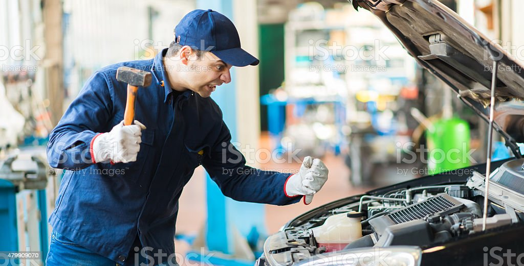 Angry mechanic smashing a car engine stock photo