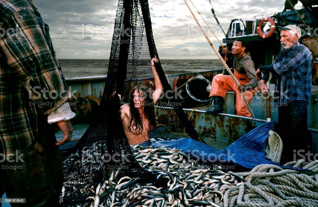 Angry Mermaid Caught in Fishing Boat Net stock photo