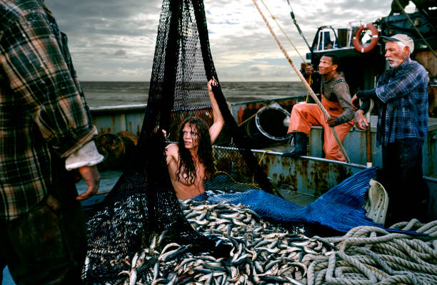 angry mermaid caught in fishing boat net - naked women with animals stock photos and pictures