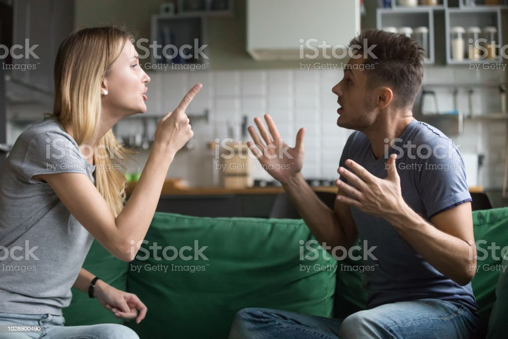 Angry millennial couple arguing shouting blaming each other of problems stock photo