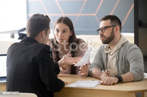 istock Angry millennial couple complaining about bad contract disputing with lawyer 963814322