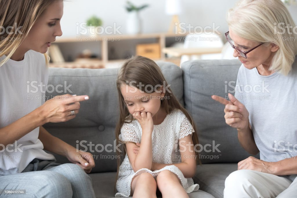 Angry Mother And Grandmother Scolding Lecturing Upset Kid Girl Together  Stock Photo - Download Image Now