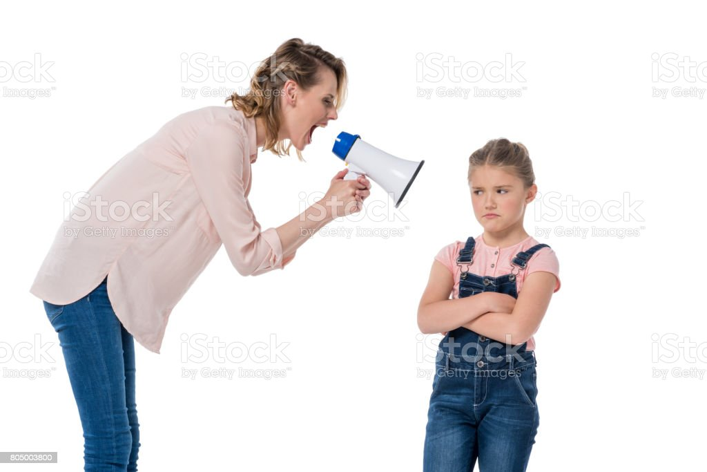 Angry mother with megaphone screaming at little daughter standing with crossed arms stock photo