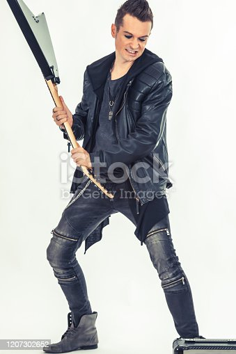 Angry musician smashing electric guitar on white background.