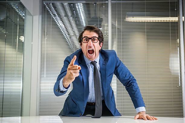 Angry Nerdy Boss Yelling Nerdy caucasian mid thirties businessman in glasses yelling. foreman stock pictures, royalty-free photos & images