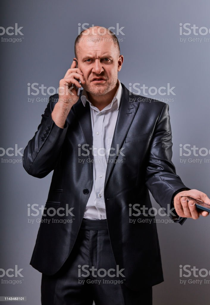 Angry not undestanding gloomy stressed angry business man talking on mobile phone very emotional in office suit on grey background. Closeup royalty-free stock photo