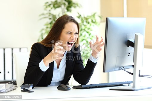 857213750istockphoto Angry office worker checking computer content 1130738897