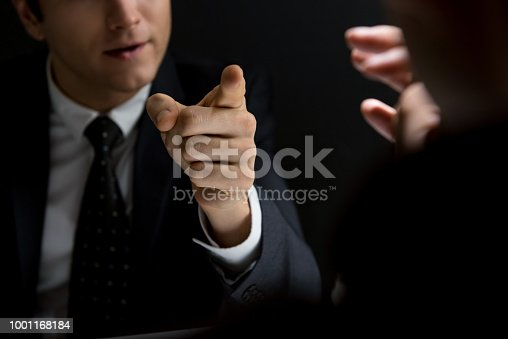 Angry official pointing hand to suspect and asking questions in dark private room - investigation and interrogation concepts