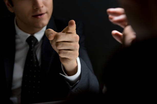 Angry official pointing hand to suspect and asking questions Angry official pointing hand to suspect and asking questions in dark private room - investigation and interrogation concepts defend stock pictures, royalty-free photos & images