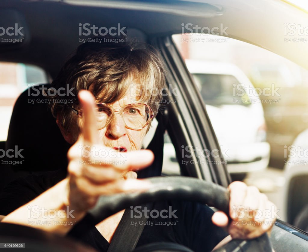 Angry old woman driver wagging finger at bad behaviour stock photo