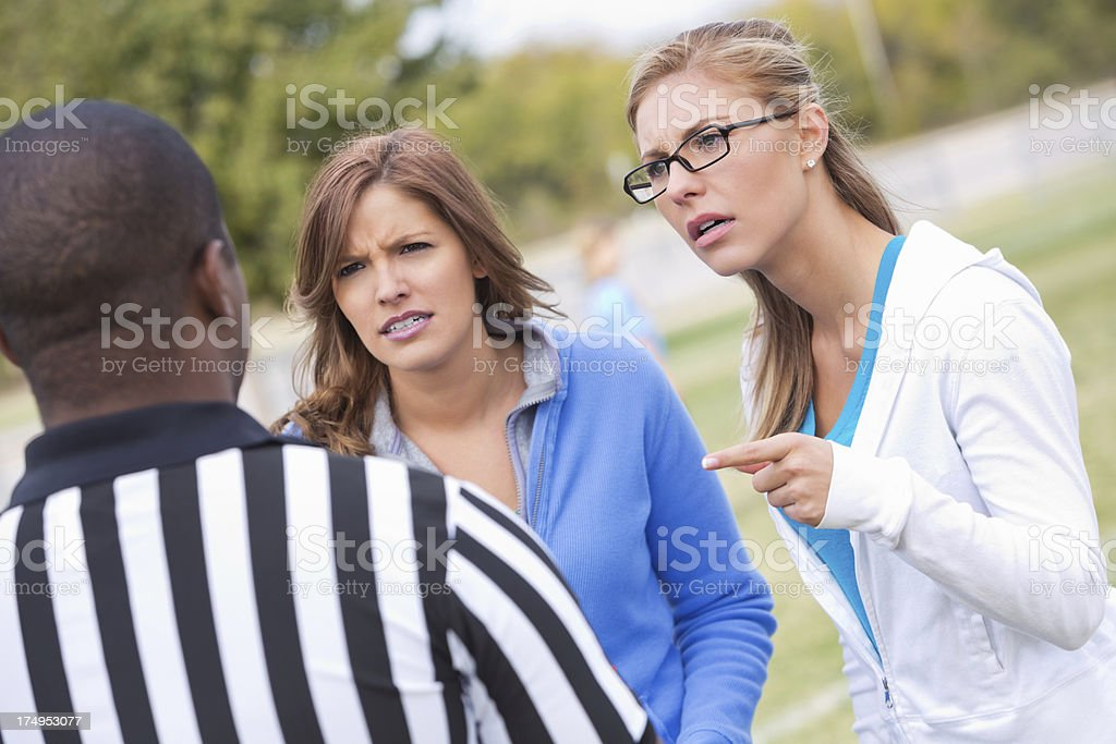 Angry parents yelling at kid's soccer referee during game stock photo