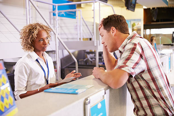 angry passenger complaining to staff at airport check in - airport check in counter stock pictures, royalty-free photos & images