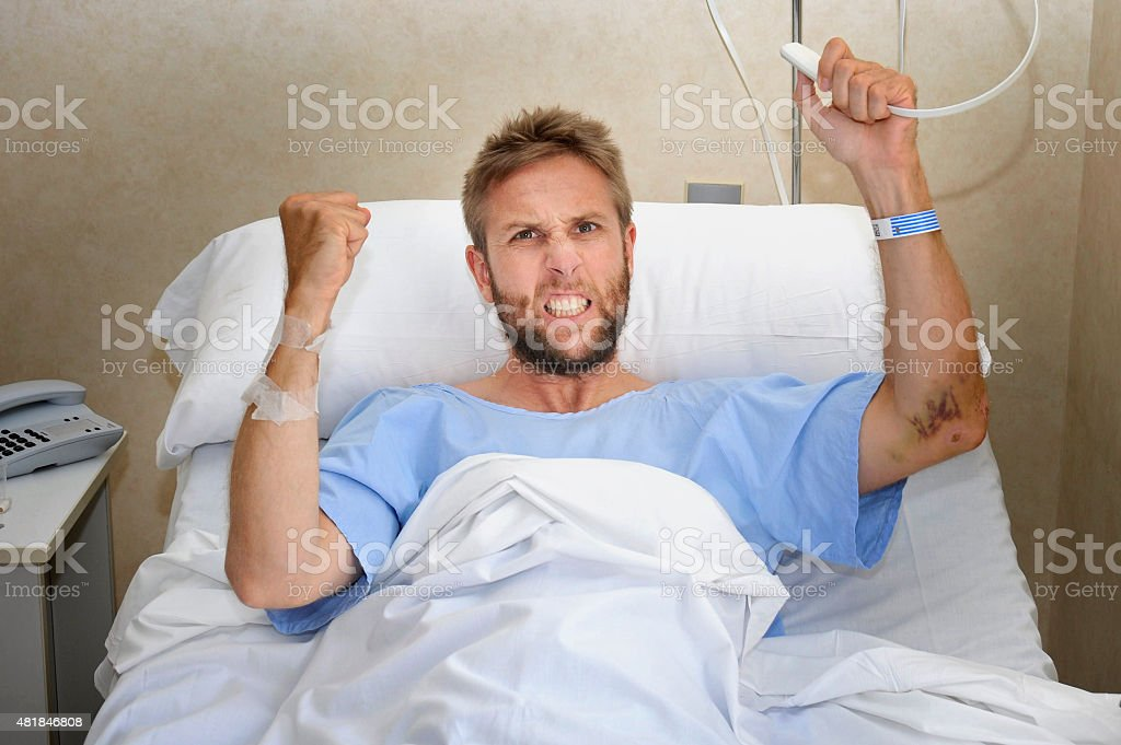 angry patient man at hospital bed pressing nurse call button stock photo