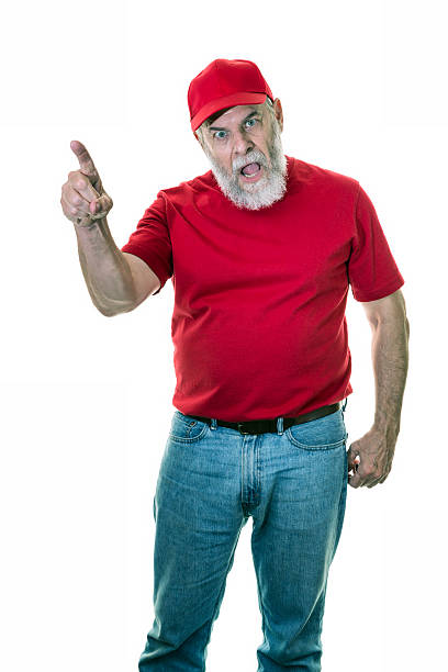 angry pointing old man redneck wearing red hat and t-shirt - unterschicht stereotypen stock-fotos und bilder