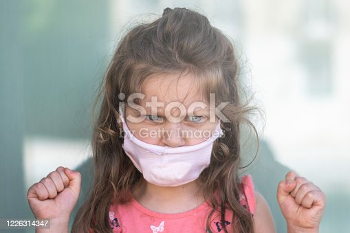 cute little girl wearing a home made surgical mask is looking angry