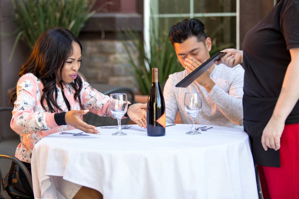 Angry Restaurant Customer Complaining to Waitress Couple on a date angry at a waitress in an outdoor restaurant.  They are upset and dissatisfied with the customer service or the food in the cafe.  The image depicts the food and service industry. bad date stock pictures, royalty-free photos & images
