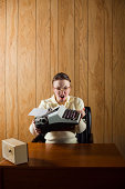 Vertical retro office portrait of an angry employee throwing a typewriter!More from this secretary shoot: