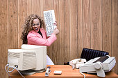 A vintage African American business woman at the office works at an old computer at her desk; she screams and prepares to smash her computer with the keyboard.  1980's - 1990's fashion style.  Wood paneling on wall in the background.