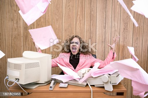 A vintage African American business woman at the office works at an old computer at her desk.  She screams and throws papers into the air in frustration.  1980's - 1990's fashion style.  Wood paneling on wall in the background.