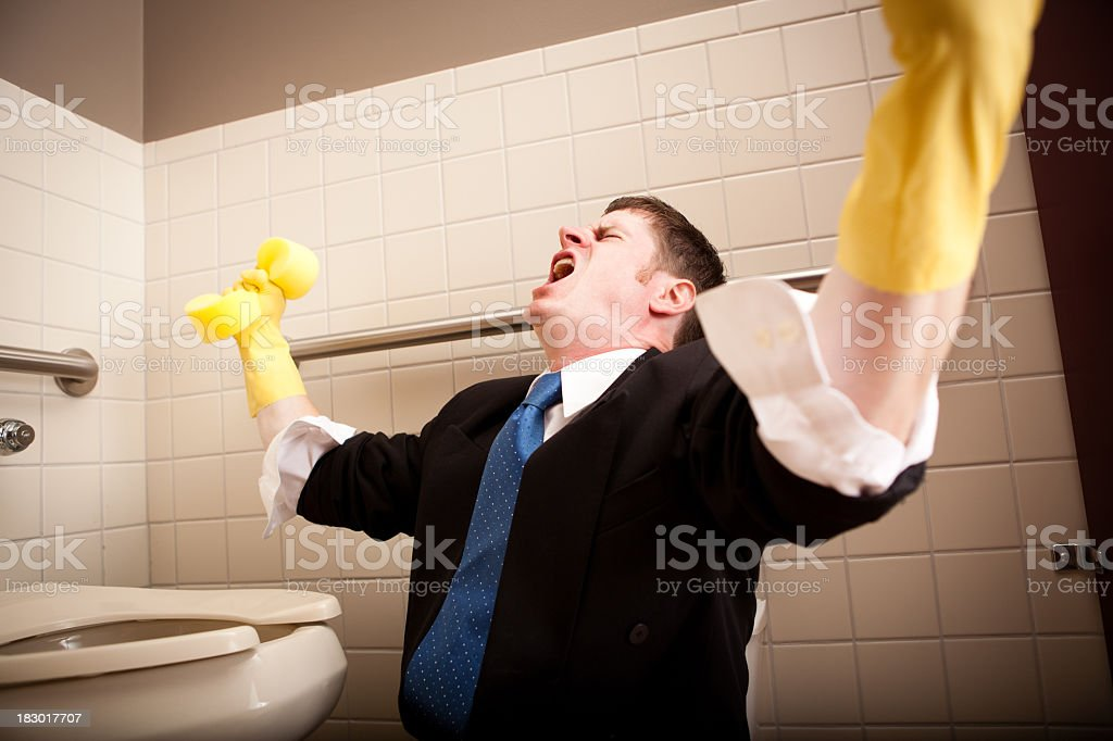 Angry, Screaming Businessman Cleaning the Restroom Toilet stock photo