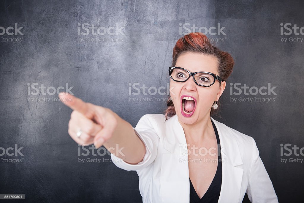 Angry screaming teacher pointing out on blackboard background stock photo