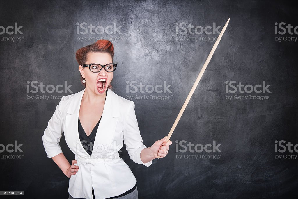Angry screaming teacher with pointer on blackboard background stock photo