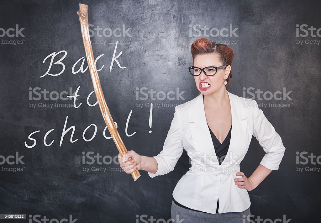 Angry screaming teacher with wooden stick on blackboard backgrou stock photo