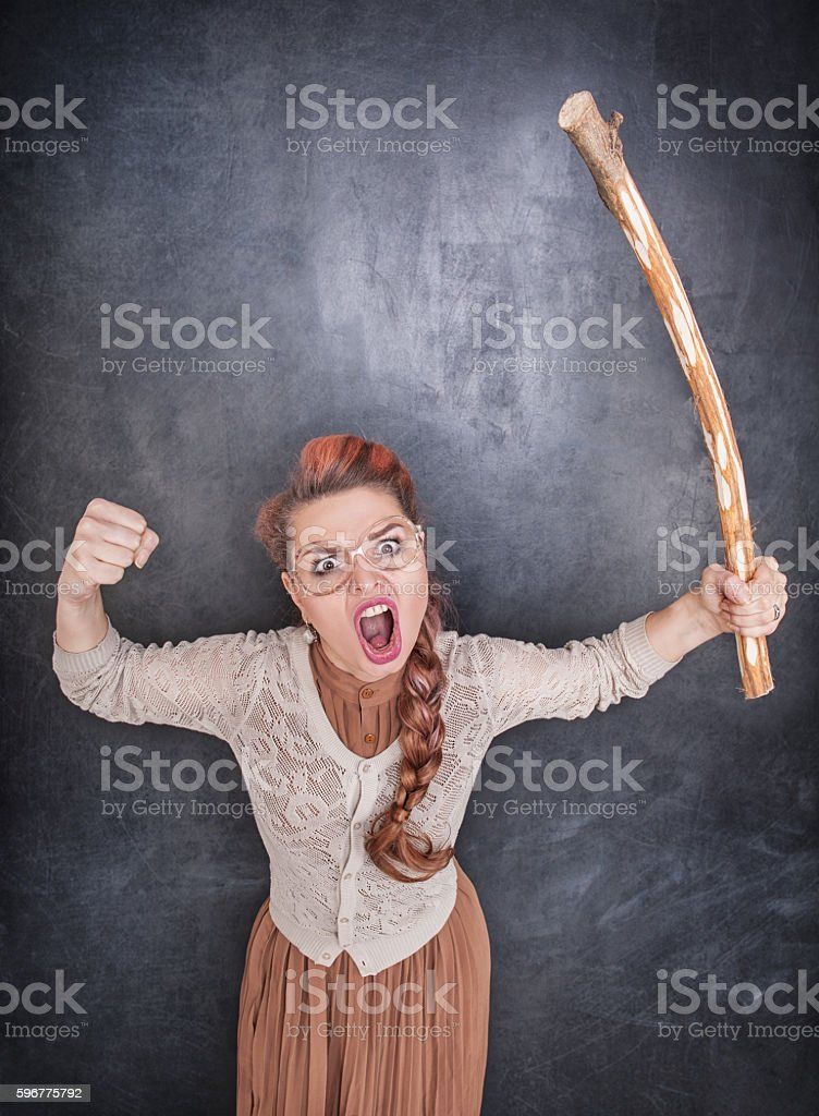 Angry screaming teacher with wooden stick stock photo