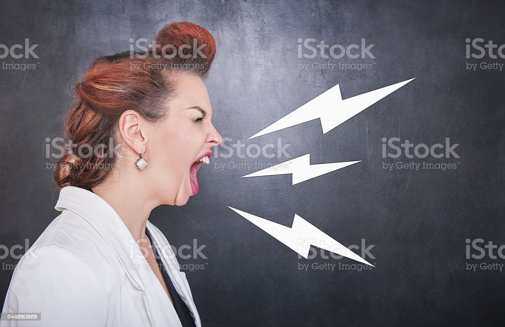 Angry screaming woman on blackboard background stock photo