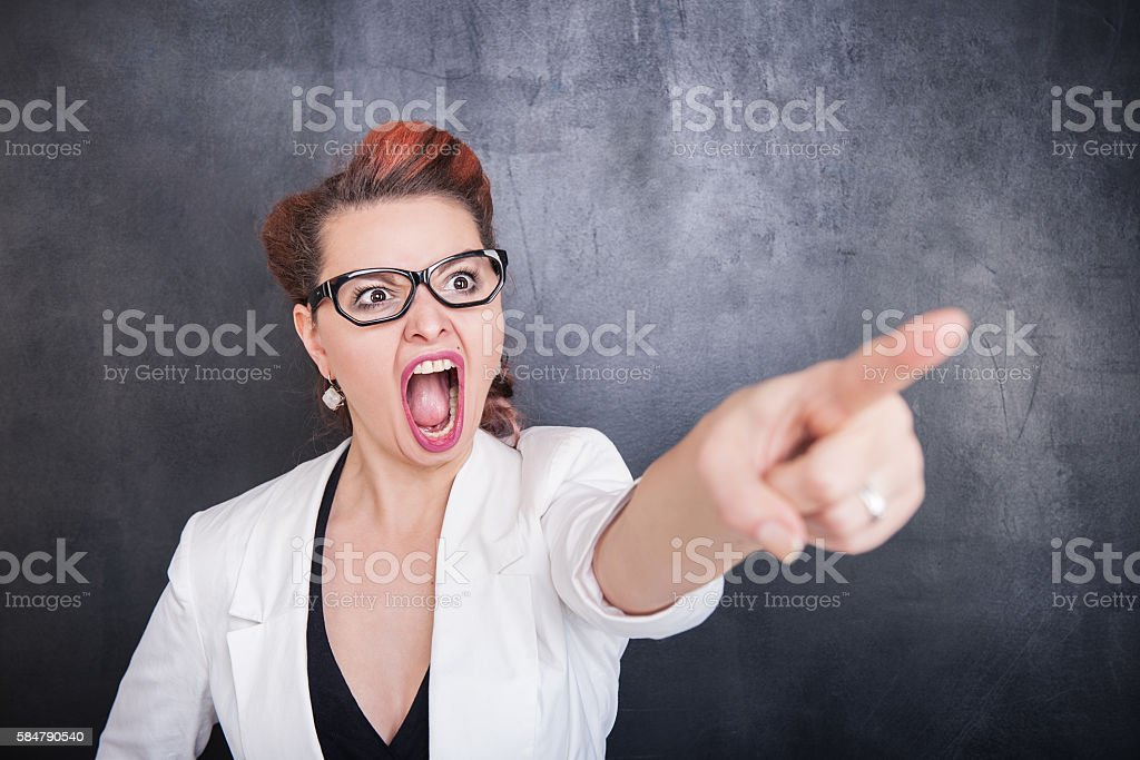 Angry screaming woman pointing out on blackboard background stock photo
