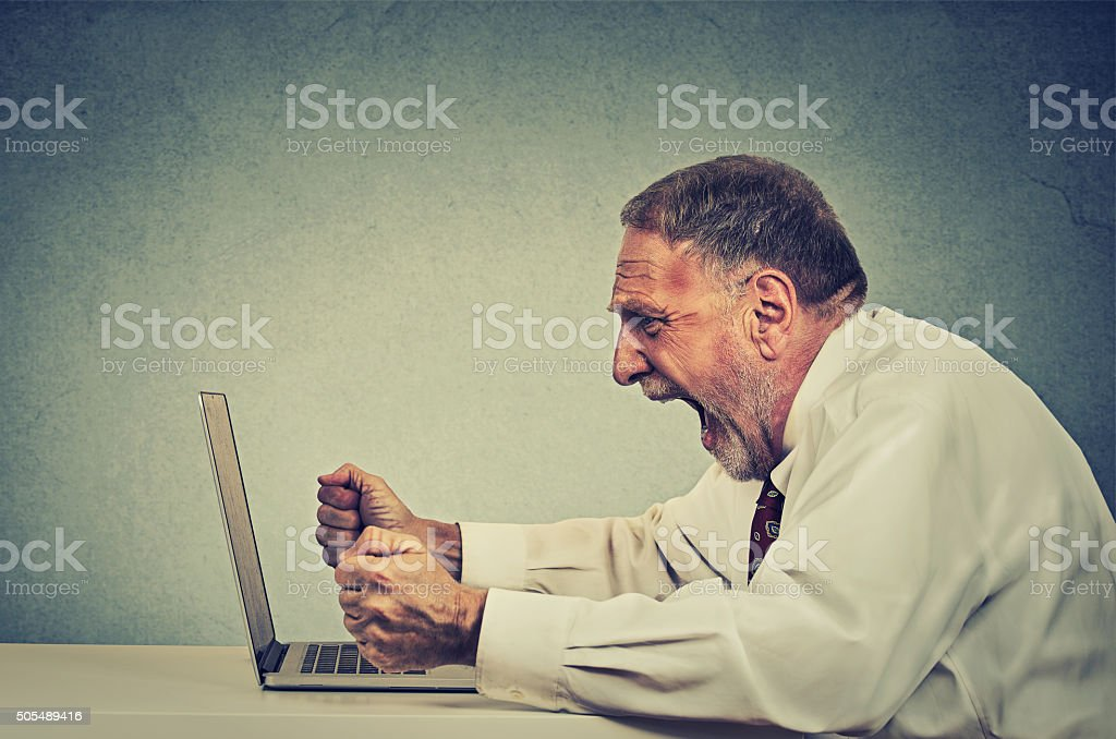 Angry senior business man working on computer screaming stock photo