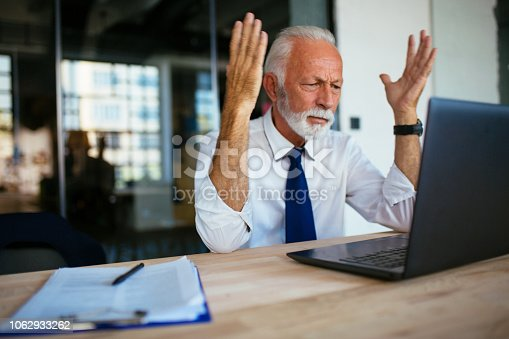 Photo of angry senior businessman at the office
