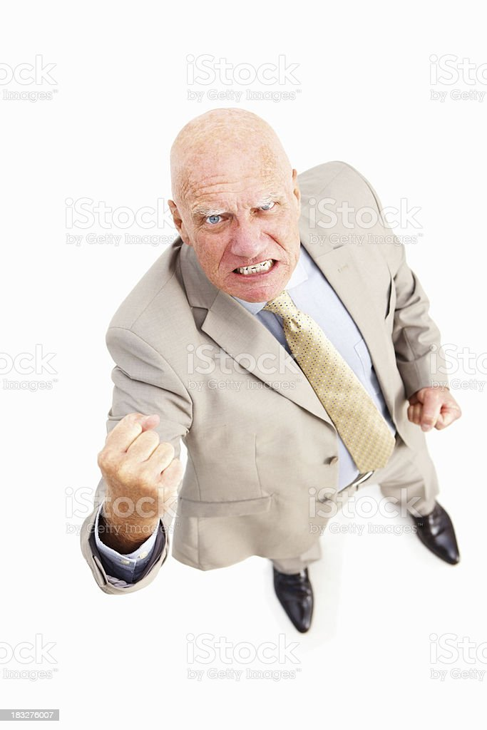 Angry senior businessman standing against white background royalty-free stock photo