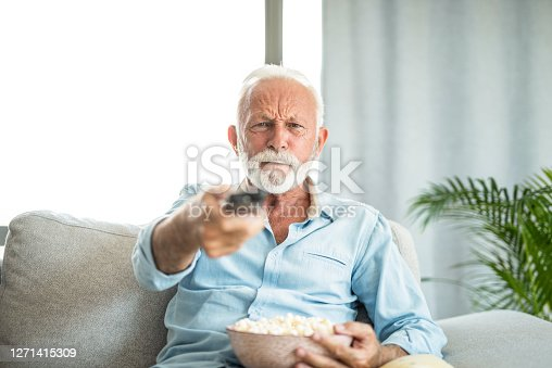 istock Angry senior man watching tv at home. 1271415309