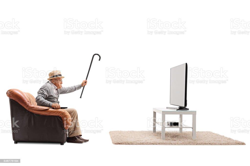Angry senior watching television stock photo