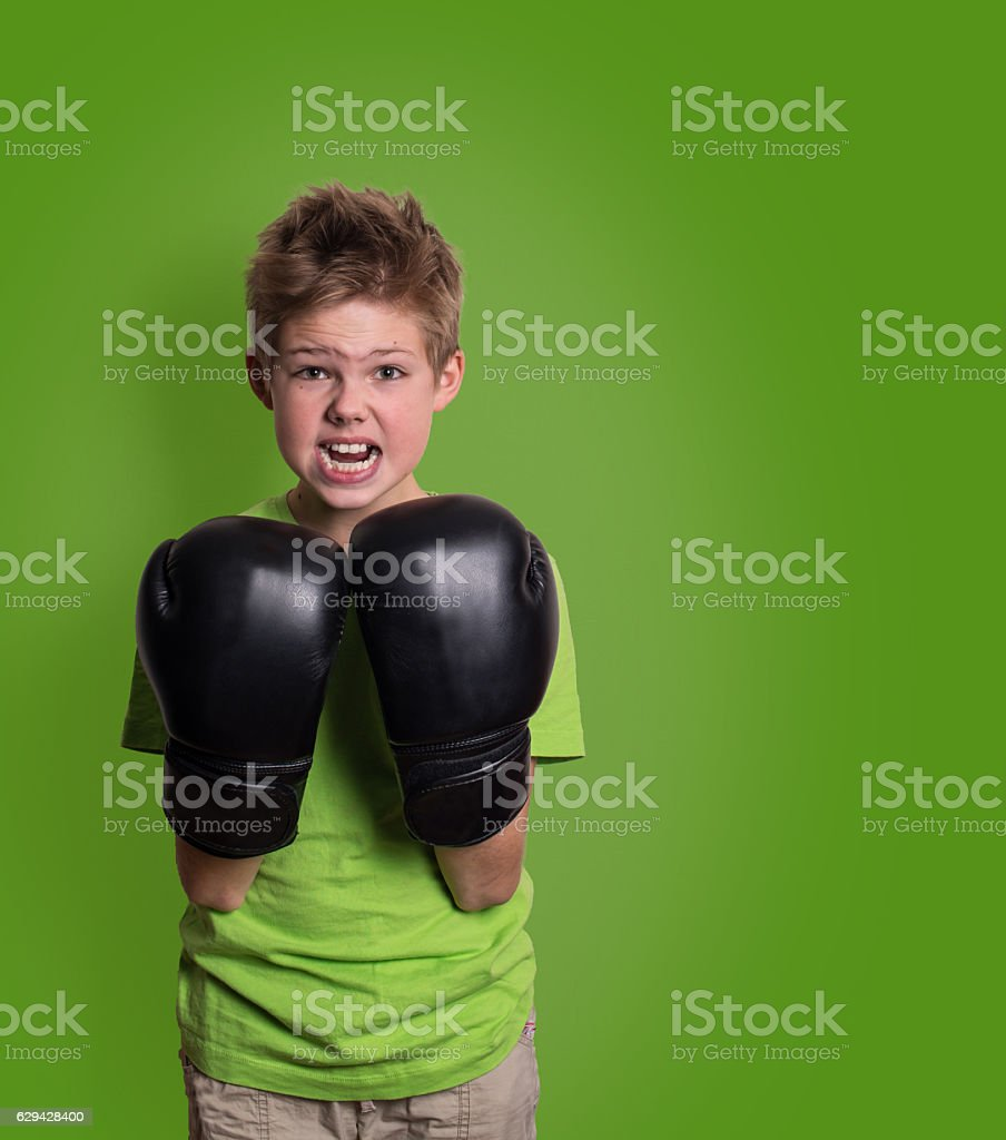 Angry shouting kid fighting with black boxing gloves isolated stock photo