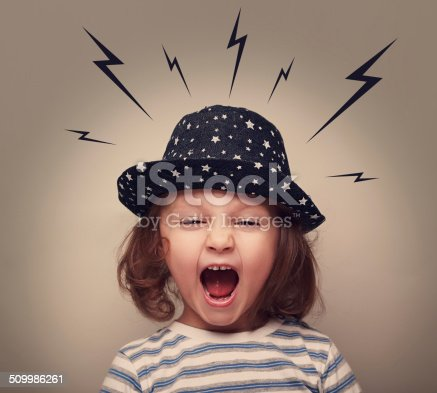 istock Angry shouting kid with lightnings above the head on grey 509986261