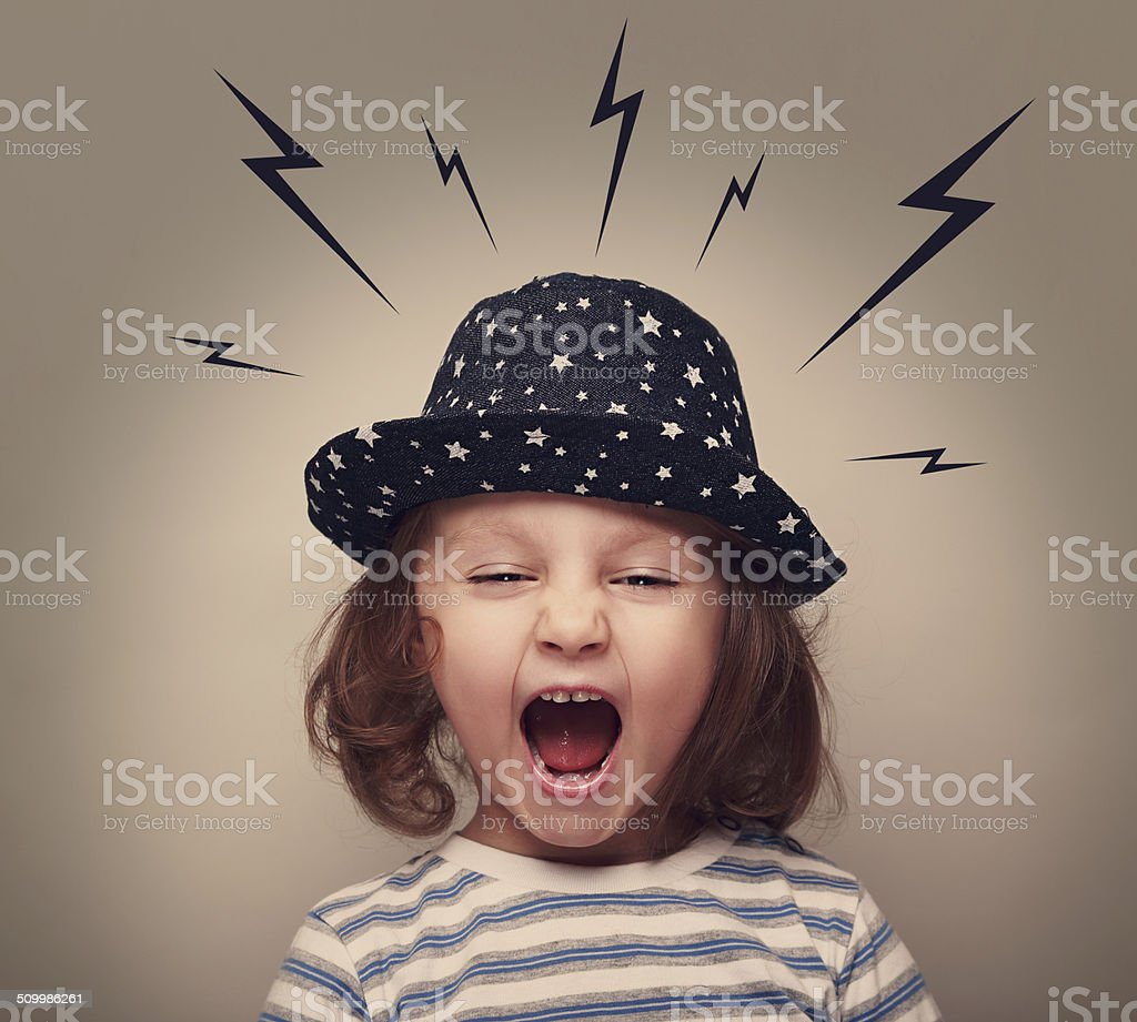 Angry shouting kid with lightnings above the head on grey stock photo