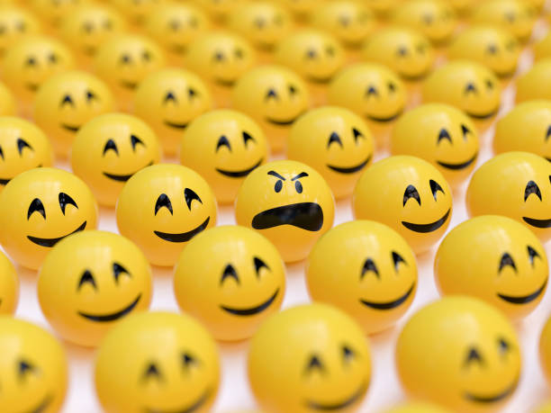 angry smiley between happy ones - emoji foto e immagini stock