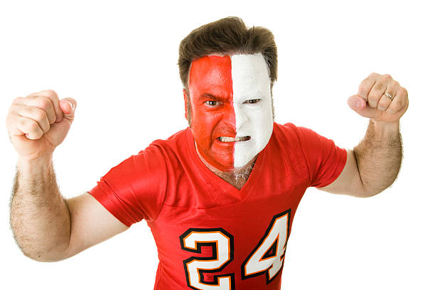 Angry Sports Fanatic Angry sports fan with a painted face, raising his fists and growling aggressively.   american football uniform stock pictures, royalty-free photos & images