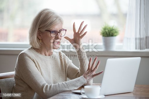 istock Angry stressed middle aged business woman annoyed with computer problem 1049512662
