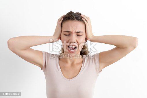 Angry stressed out young woman plugging ears with fingers