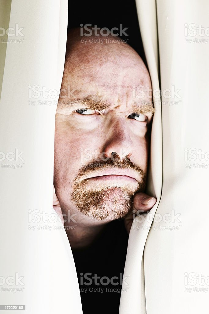 Angry, suspicious man frowns sideways through closed curtains stock photo