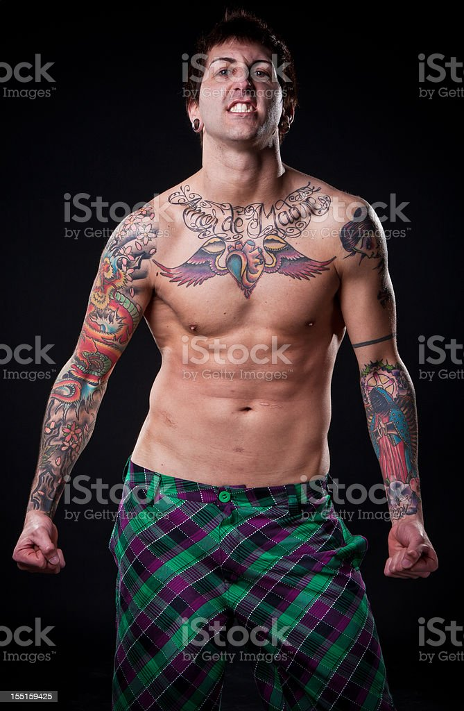 Angry tattooed man flexing his muscles. royalty-free stock photo