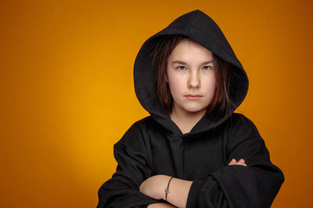 angry teenage girl in black hood with confident eyesight looking straight at camera stock photo